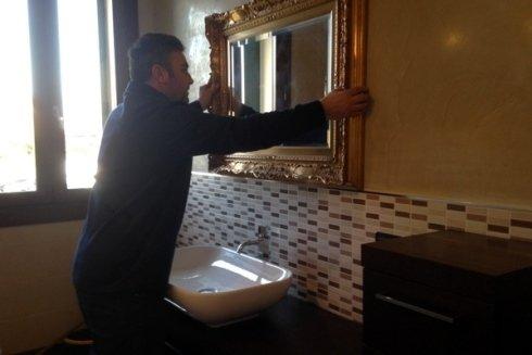 addetto mentre monta uno specchio sopra il lavello di un bagno