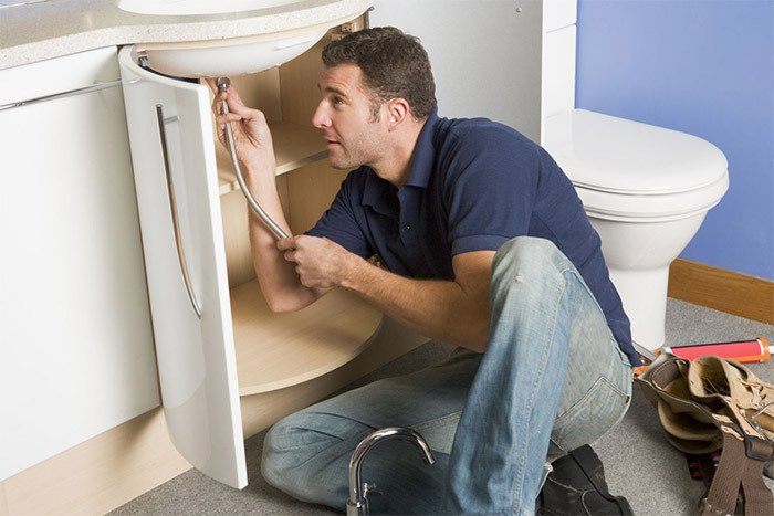 Plumber unblocking sink