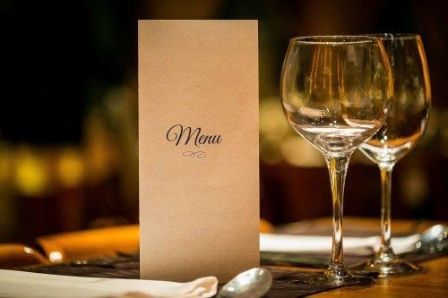 Menu con due bicchieri di vino bianco