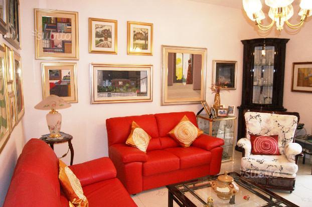 salotto con divani rossi e quadri appesi al muro