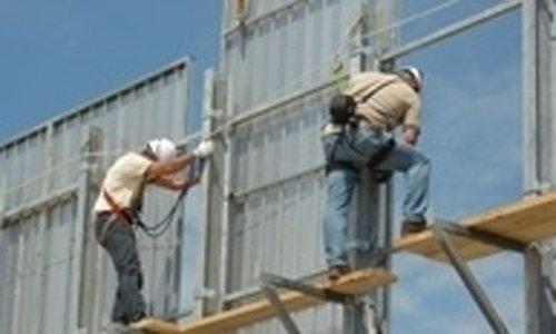 operai installano cartelloni pubblicitari