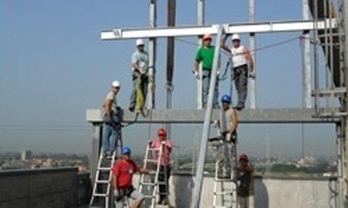 operai su tetto per installazione insegna