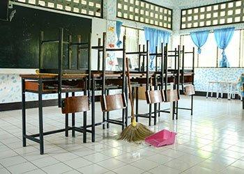 inserviente pulisce pavimento di una scuola