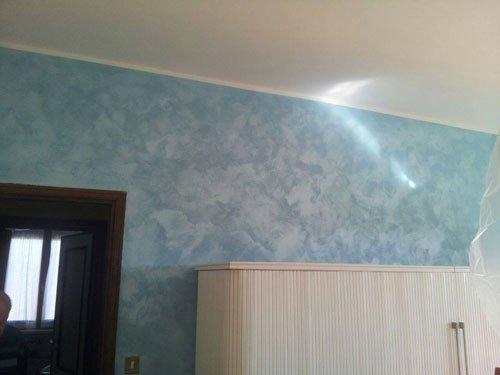 una parete color celeste e un armadio bianco
