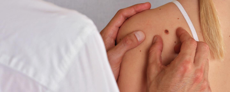 Medico durante una visita dermatologica su una donna in clinica