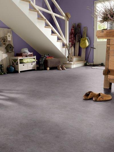 dettaglio di un salotto con pavimento grigio e pareti lilla