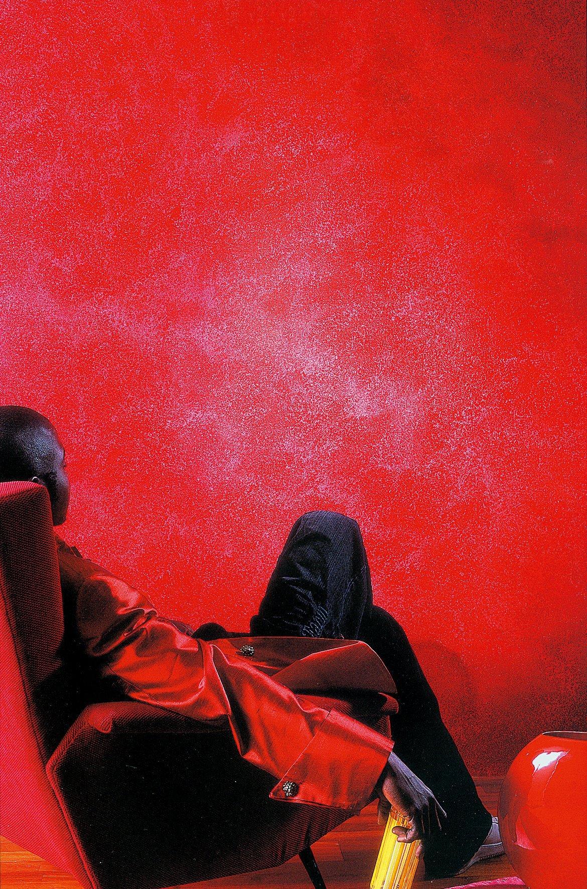un ragazzo seduto di spalle su una poltrona rossa