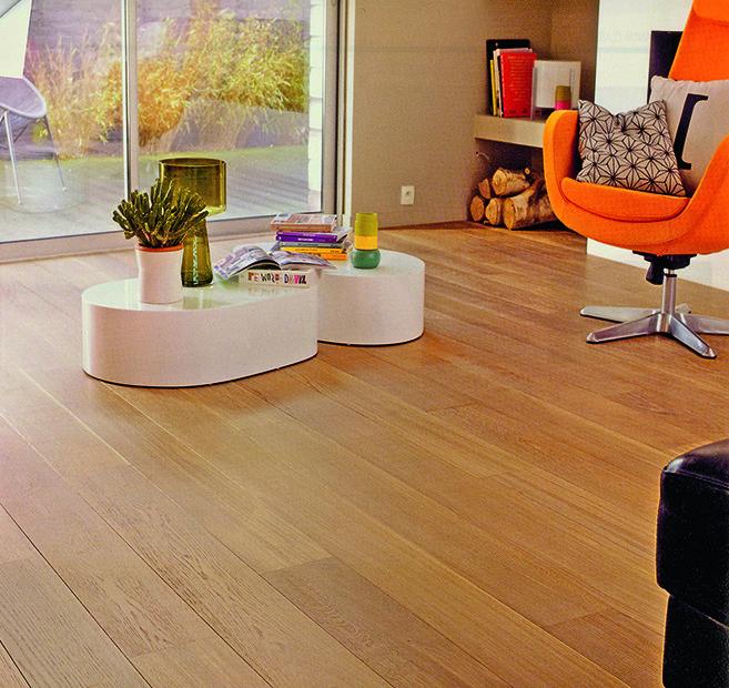 dettaglio di una salotto con un parquet chiaro e un tavolino bianco con delle riviste
