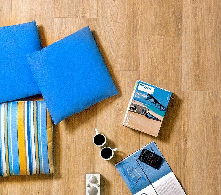 vista dall'alto di un laminato chiaro con due tazzine da caffè. tre cuscini e delle riviste da viaggio