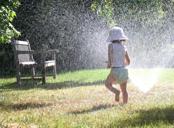 Small child playing around water sprinklers in Kailua, HI