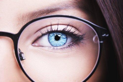 occhio azzurro femminile con occhiali