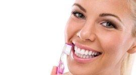 ragazza che sorride, denti bianchissimi, spazzonlino da denti in mano