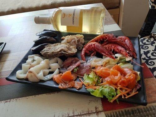 piatto con pesce fresco verdura e una bottiglia di vino