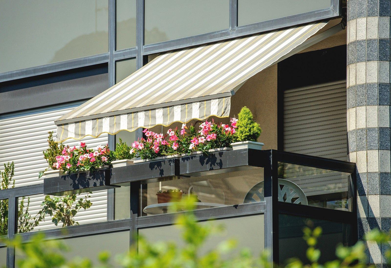 Balcone con tenda aperta e bellissimi fiori
