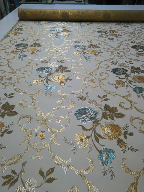 una stoffa di color bianco con dei ricami dorati e dei fiori di color azzurro
