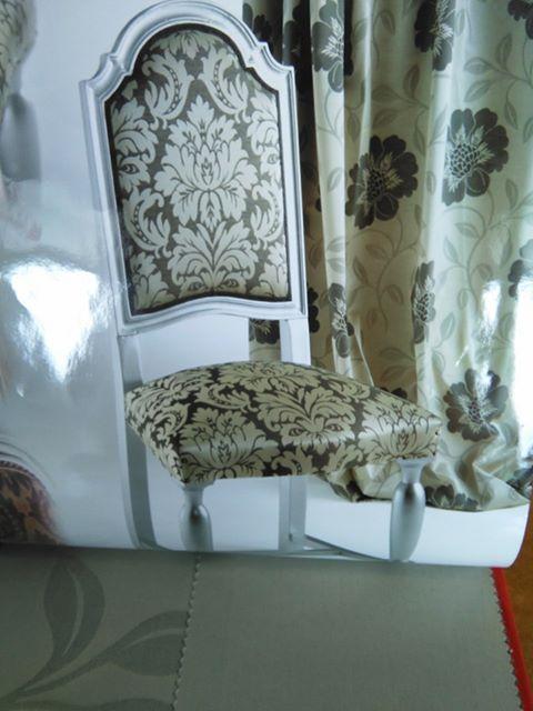 una sedia di legno con dei cuscini imbottiti in stoffa con dei disegni