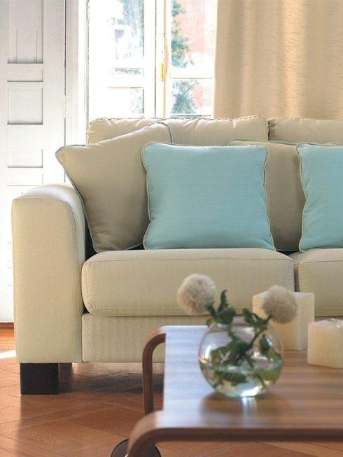un divano di color beige con dei cuscini di color azzurro e beige