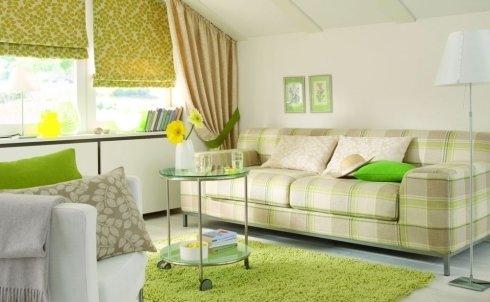 un divano a tre posti con disegni a scacchi  di color beige e verde