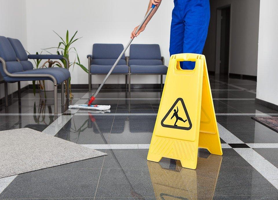 Uomo lavando il suolo e il cartello di avvertimento di suolo bagnato