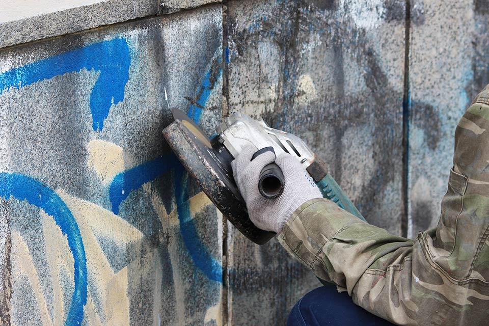 Uomo puliendo una parete per cancellare il graffiti