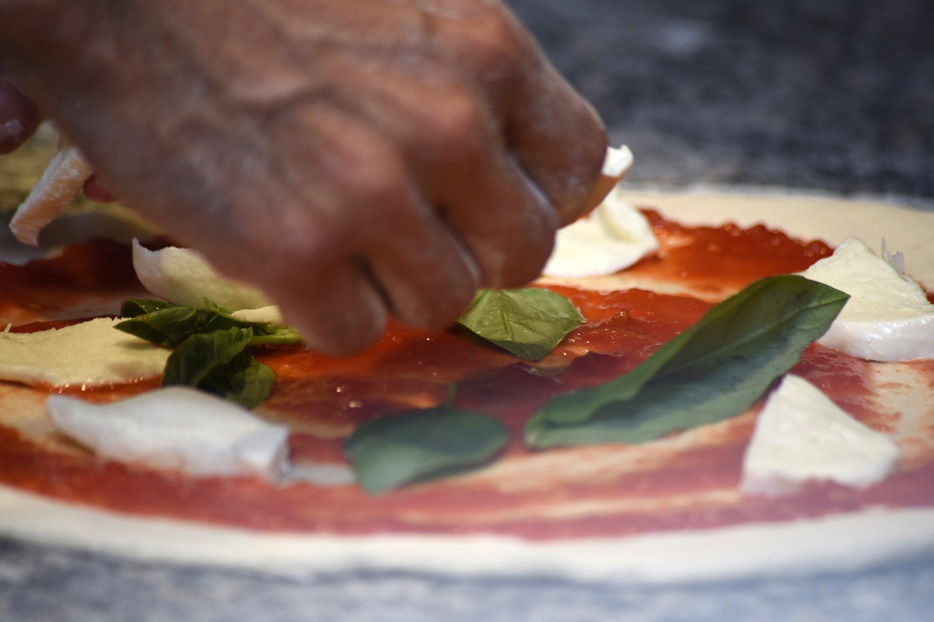 Il pizzaiolo prepara una pizza margherita con mozzarella di bufala