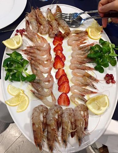 persona che prende una porzione di pesce crudo con cucciaio e forchetta