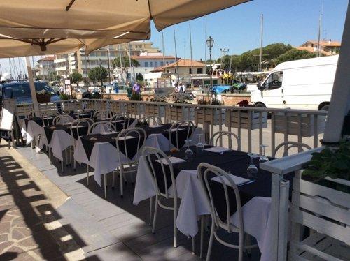 fila di tavoli apparecchiati nella zona esterna del ristorante