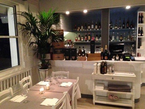 vista del ristorante con tavolo apparecchiato e bancone del bar