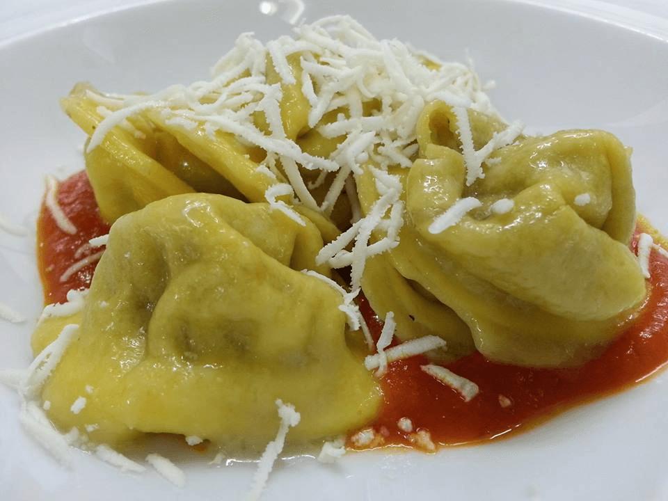 dei ravioli con del formaggio e del sugo