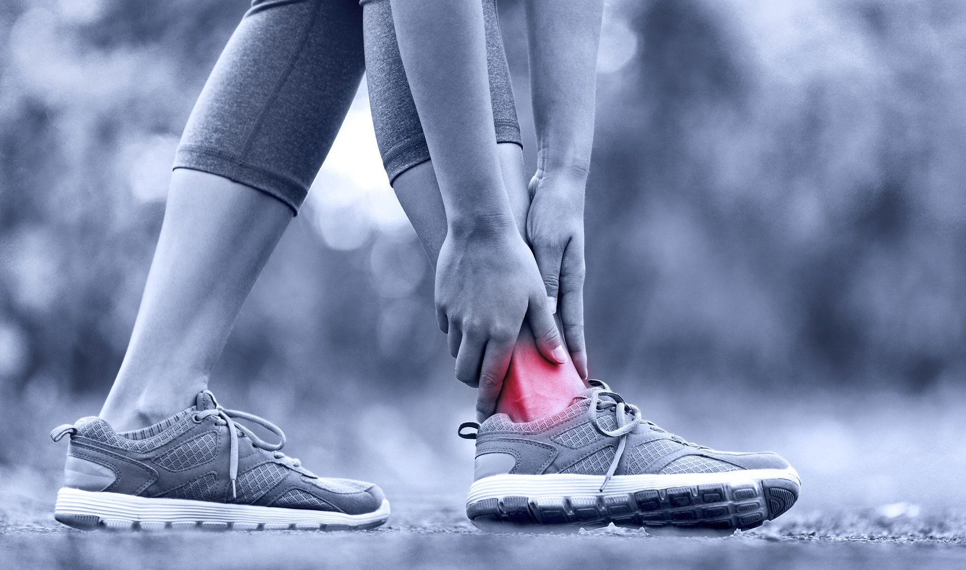 A lady in leggings and trainers with her hands on her ankle, where the painful area is shown in red.