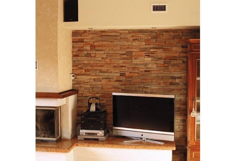 muro di mattoni con televisione appoggiata su una mensola in marmo