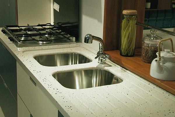 due lavelli in alluminio e un fornello su una superifcie bianca