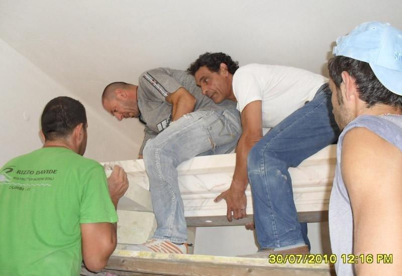 addetti mentre cercano di sollevare una struttura in marmo