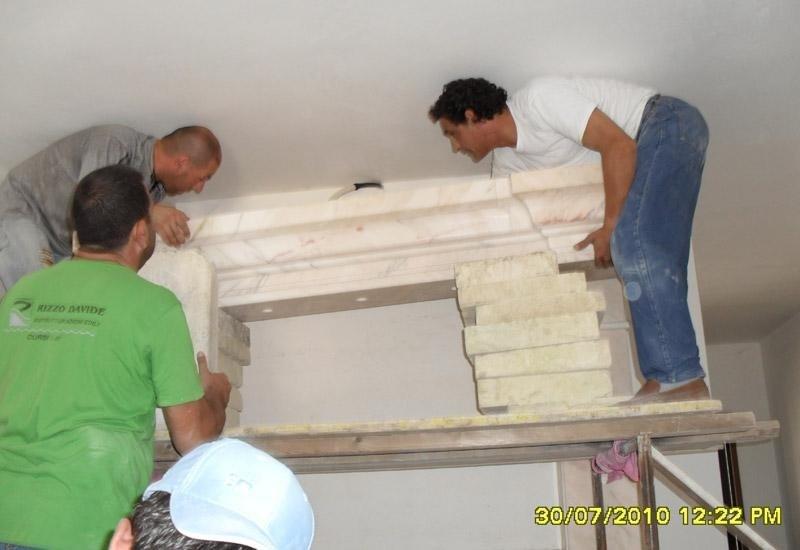 addetti mentre spingono una struttura in marmo