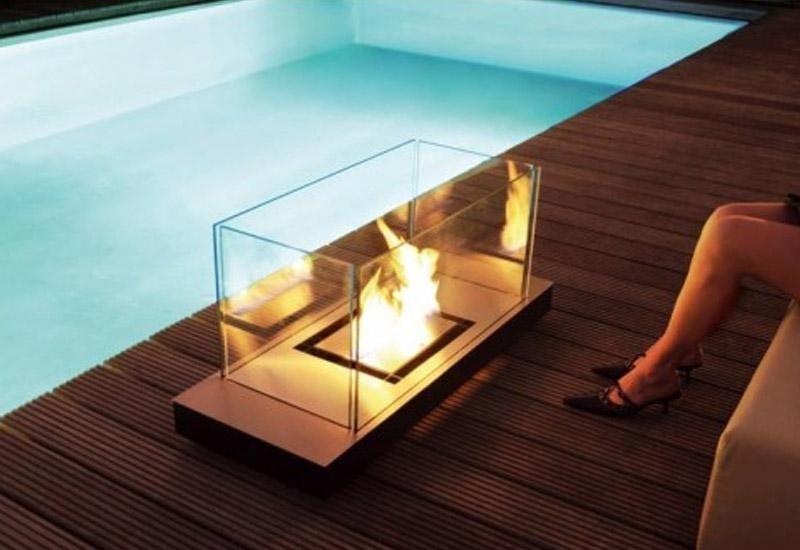 camino con teca trasparente vicino a una piscina