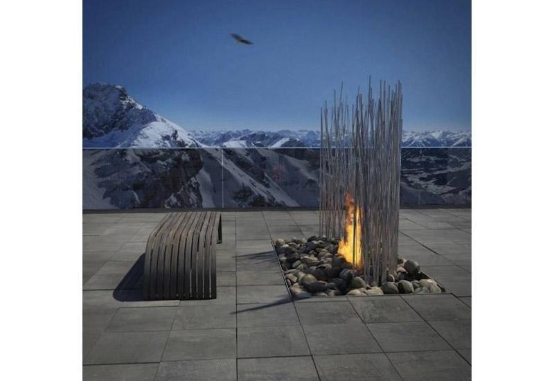 fiamma del focolare con sassi e montagne all`orizzonte