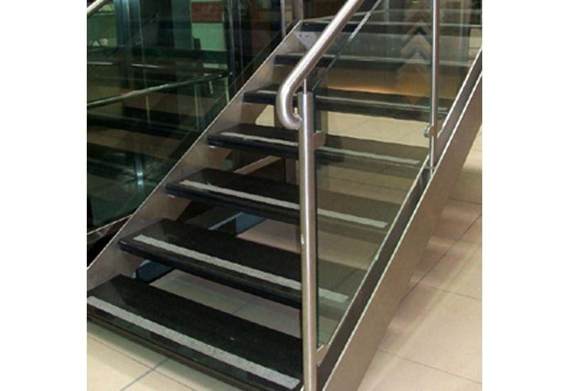 scale in marmo nere con ringhiera in ferro e parapetto in vetro