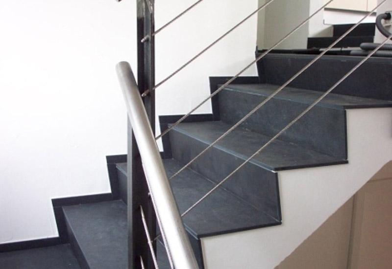 particolare di una scalinata in marmo e ringhiea in ferro