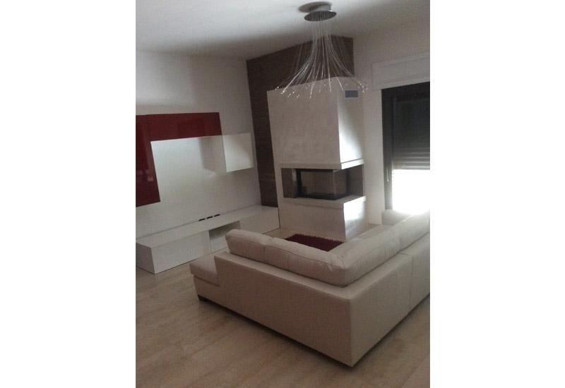 camino in marmo con divano sul lato e lampada moderna