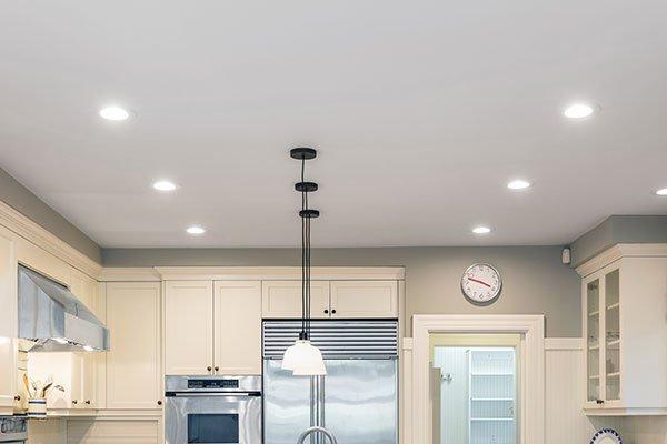 una cucina in una casa e in mezzo tre lampade a sospensione