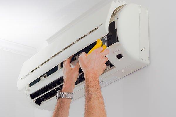 due mani con in mano una pinza gialla che stanno per riparare un condizionatore