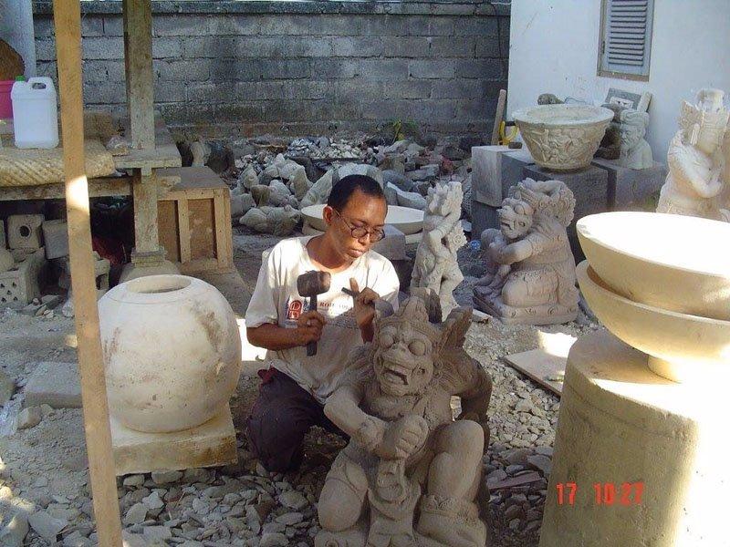 uomo scolpisce su roccia  statua tradizionale