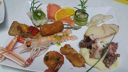 un piatto con scampi, filetti di pesce, polipo e alcuni pesci fritti