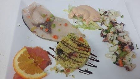 un piatto con polipo alla catalana, carpaccio di pesce e salsa cocktail