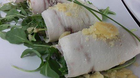 dei filetti di pesce arrotolati e rucola