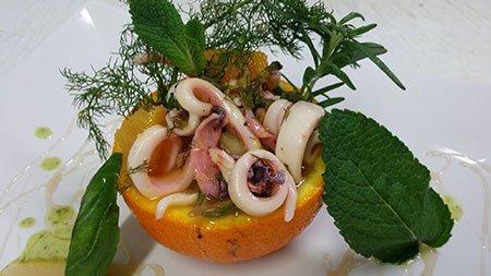 un piatto con polipo e anelli di calamari servito in una buccia di arancia