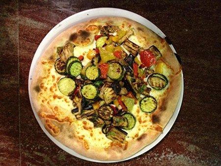 una pizza bianca con delle verdure grigliate