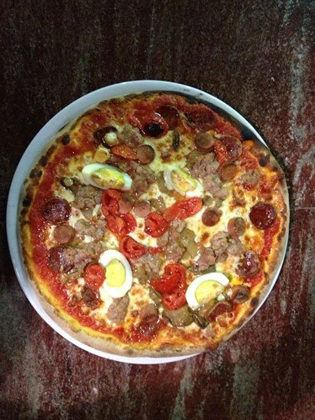 una pizza con salsiccia e uova sode