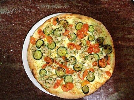 una pizza con gamberi e delle zucchine grigliate