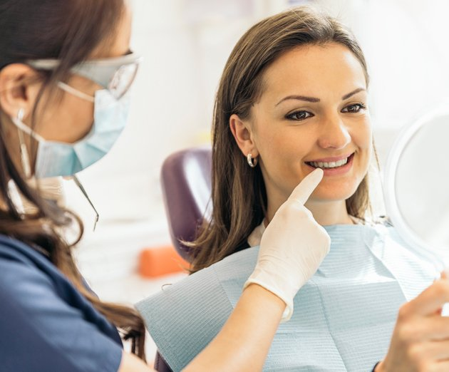 dental vision young woman checking teeth in mirror